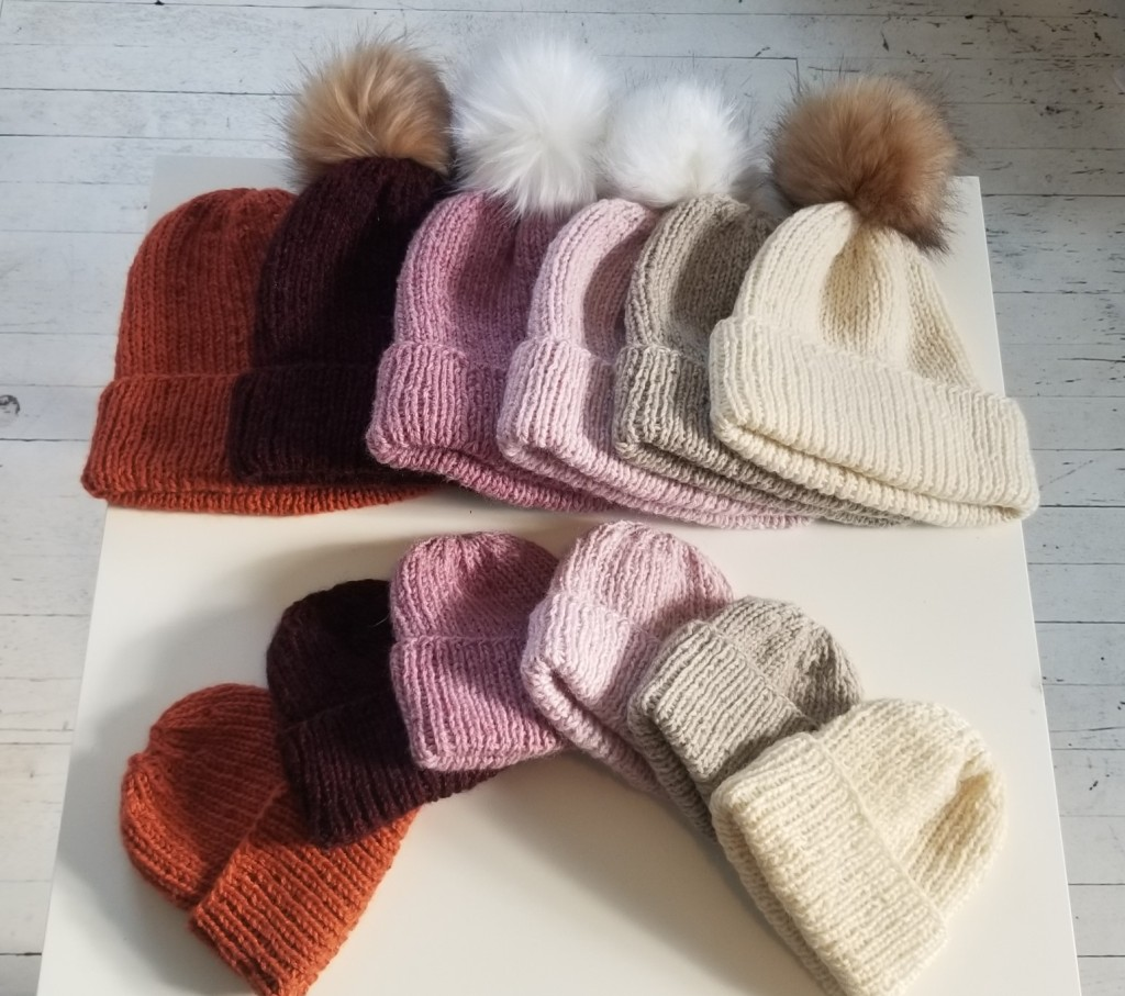 Image of a dozen ribbed hats in different colors and sizes