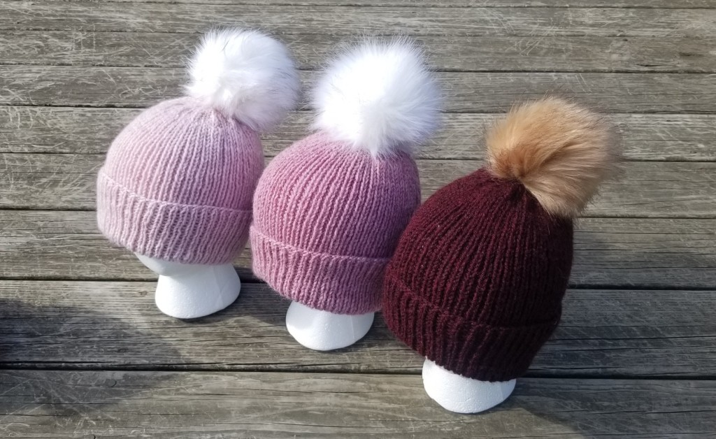 Image: of three Anchor handknit ribbed hats in burgundy, dark rose, and light rose.