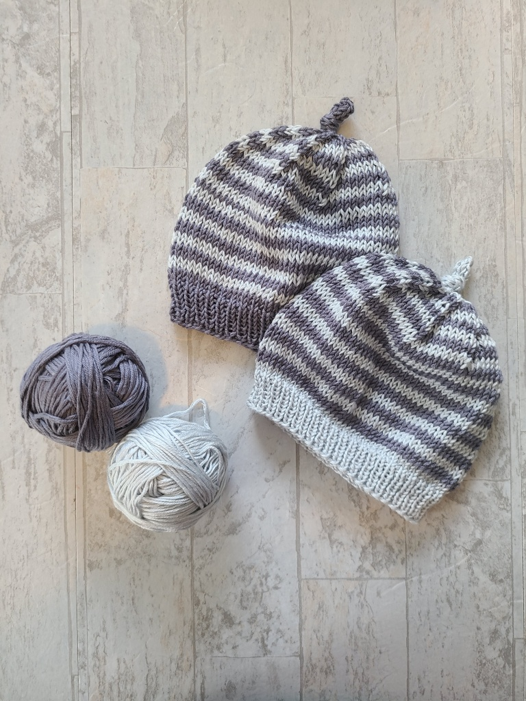Image of the two leftover balls of Nuboo yarn and two of the Starboard hats with opposite stripe patterns.