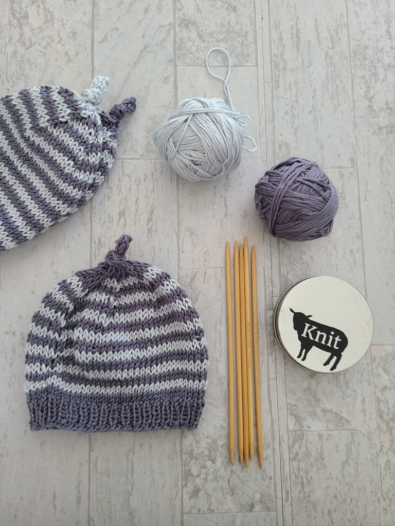 Image of two folded and stacked hats, two balls of yarn, one hat laying flat, a set of double pointed knitting needles, and a notions tin.